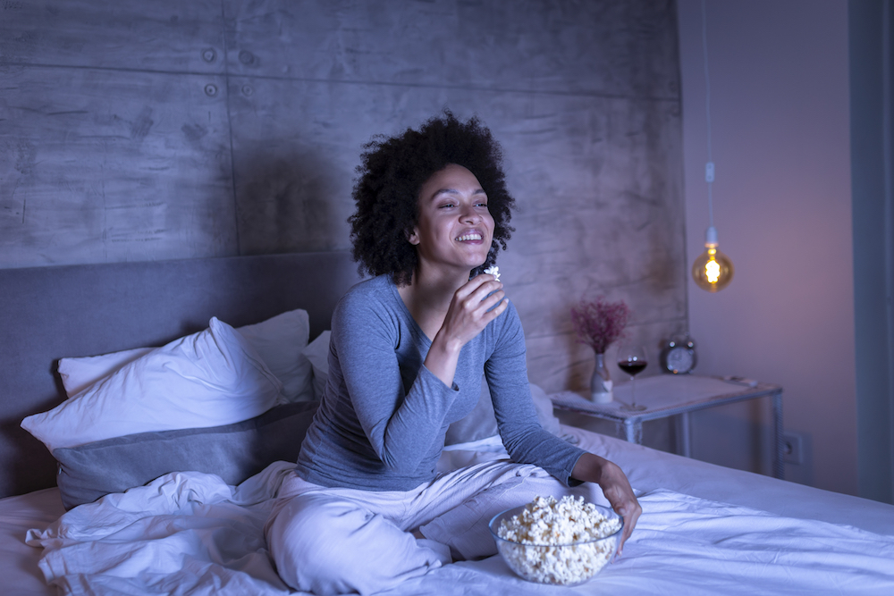 Beautiful mixed race woman wearing pajamas sitting on bed, eating popcorn and watching a comedy movie on TV, relaxing at home late at night