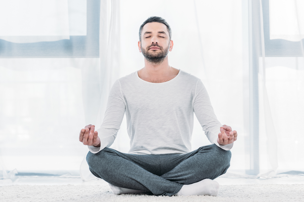 good-looking man with eyes closed sitting on carpet in Lotus Pose and meditating at home