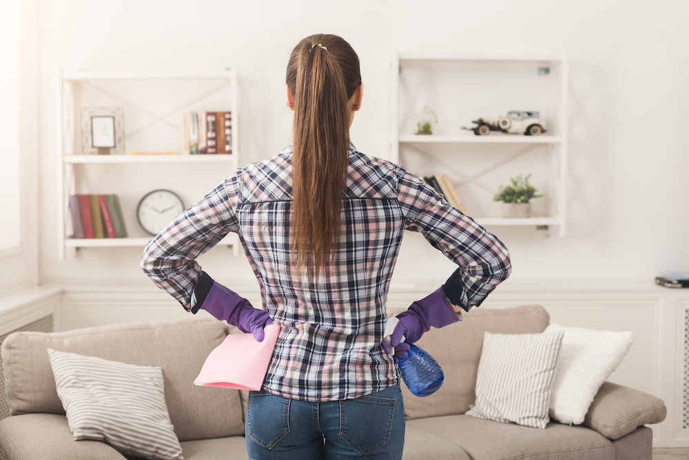 Unrecognizable woman with cleaning equipment ready to clean house. Cropped girl holding rag and spray detergent, professional cleaning service concept, copy space, back view
