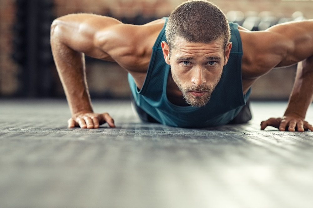 Young athlete doing push ups as part of bodybuilding training. Muscular guy doing a pushup on floor at crossfit gym. Determined athletic guy in sportswear exercising.