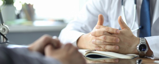 Close-up of doctor and patient hands while doctor listens to patient complaints. Male doctor giving a consultation to a patient and explaining medical information and diagnosis