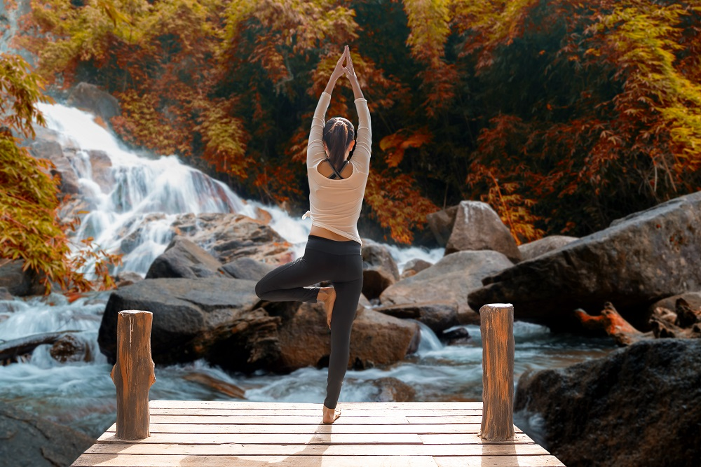 Healthy woman lifestyle balanced practicing meditate and zen energy yoga on the bridge in morning the autumn waterfall in nature. Healthy life Concept.