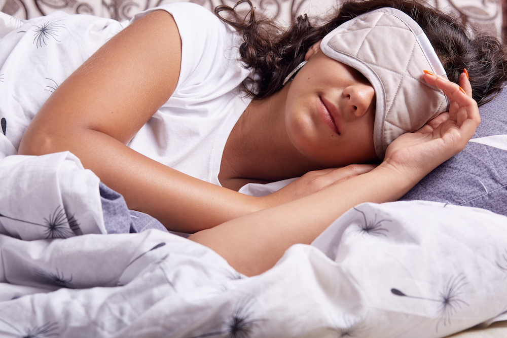 Image of young woman sleeping with eye mask, lying under cosy blanket in comfortable bed at home, brunette lady with wavy hair, lady relaxing, does not need to go anywear, having rest, sleeping.