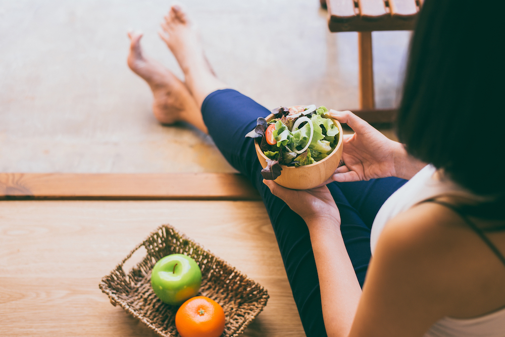 Woman hands holding and eating healthy salad for breakfast in the morning