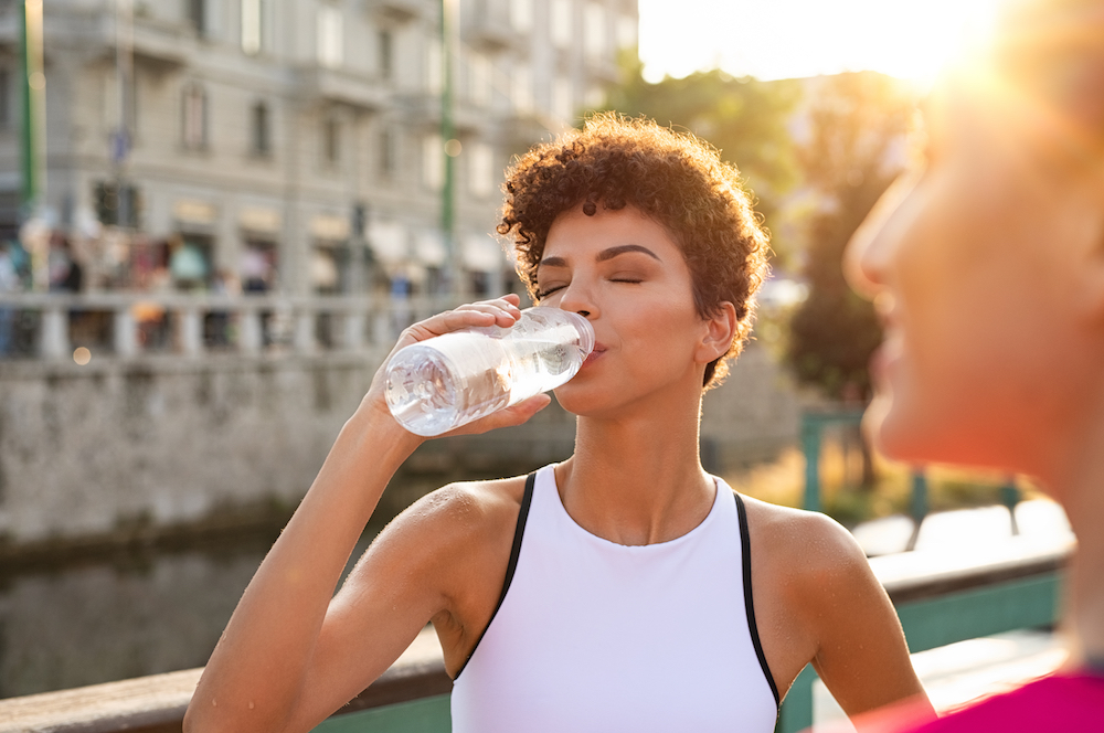 Young african woman drinking water after jogging. Athlete girl resting while drinking water after workout exercise. Sport brazilian woman resting after running exercise.